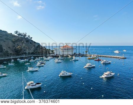 Aerial View Of Catalina Casino And Avalon Harbor With Sailboats, Fishing Boats And Yachts Moored In