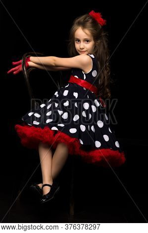 Pretty Girl Wearing Retro Style Polka Dot Dress, Red Gloves And Bow Sitting On Chair Posing At Camer