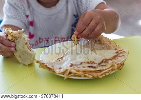Homemade Traditional Russian Pancakes With Condensed Milk. Childrens Hands And Pancakes. The Child I