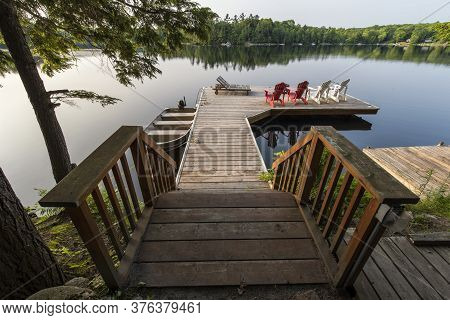 Two Muskoka Chairs Sitting On A Wood Dock Facing A Calm Lake. Across The Water Is A White Cottage Ne