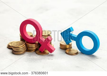Discrimination Of Men. A Large Stack Of Coins And A Gender Symbol Of A Woman And A Small Stack Of Co