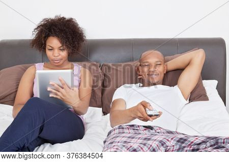 Young man watching TV while woman using tablet PC in bed