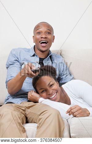 Excited young African American couple watching TV