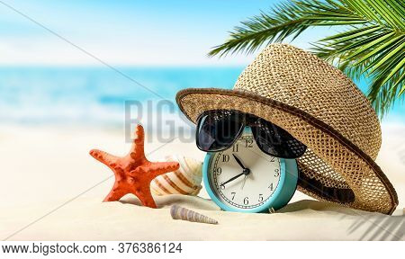 Summertime Vacation Concept. Time To Relax. Alarm Clock With Straw Hat, Starfish On The Sand Beach A