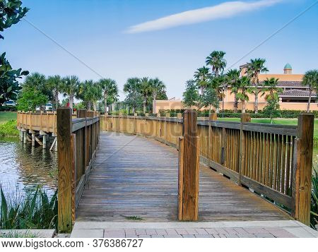 Short Pedestrian Zigzag Wooden Bridge Over A Small River In Tropical Region
