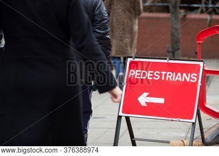 Close-up of pedestrians arrow sign on sidewalk