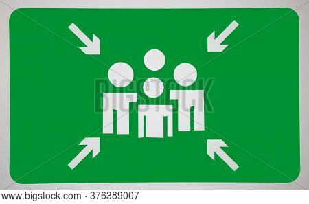 Arrow signs towards human representation on green surface