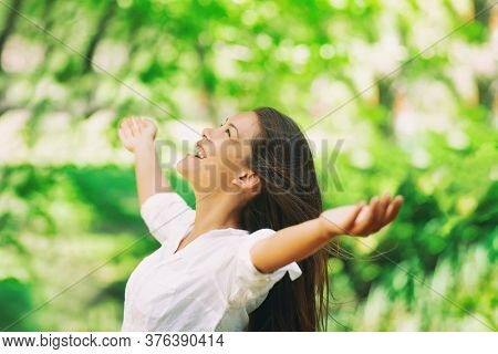 Happy woman breathing fresh clean air outdoor nature forest for spring season pollen allergies. Carefree Asian girl with arms outstretched in freedom. Happiness outside.