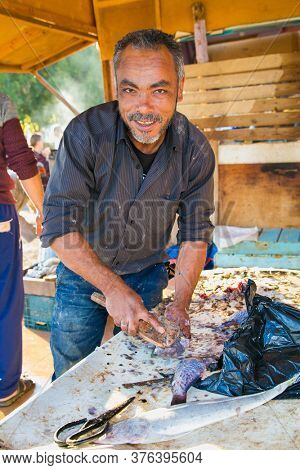 Hurgada, Egypt-Jan 30, 2020.  An Egyptian cleans fish at a fish market in Hurghada, Egypt.