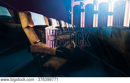 A Row Of Yellow Seat With Popcorn On Chair In The Movie Theater