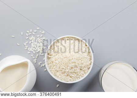 Vegan Rice Milk With Rice Grains On Gray Background. Copy Space, Top View