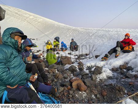 Elbrus District, Russia - July 7, 2020: Group Of Climbers With Backpacks And Trekking Poles On A Hal
