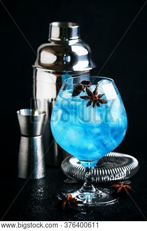 Blue Cocktail With Ice And Anise In Brandy Glass, Black Background, Selective Focus