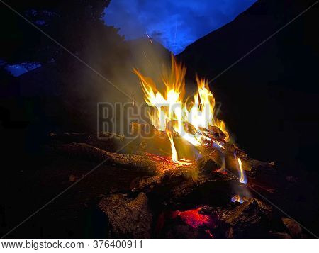 A Large Flaming Bonfire With Sparks And Particles In Front Of A Forest In The Mountains. Bonfire At