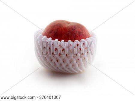 Autumn harvested peach in protective  foam net sleeve or flexible polyethylene Foam Packaging Mesh Netting. Isolated on white.