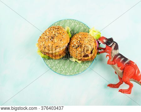 Vegan Burger With Soy Vegetable Patty And Veggies On Green Plate Being Attacked By Toy Dinosaur. It