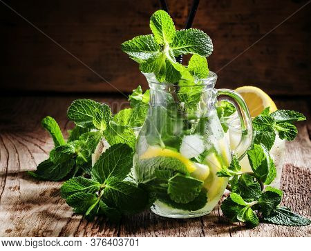 Summer Citrus Lemonade With Peppermint, Lemon, Green Tea And Ice Cubes In A Glass Pitcher, Vintage W