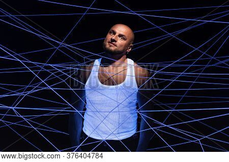Picture Of Bald Man Tangled In White Threads In Ultraviolet