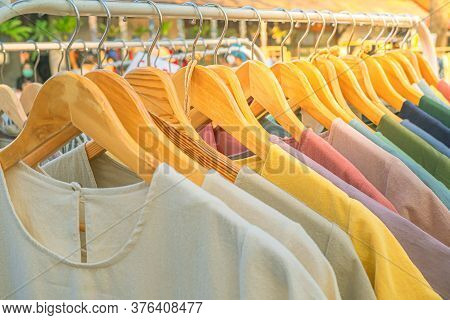 Bright Colored Clothes On Wooden Hangers On The Market, Clothes Shop In The Outdoor Market, Clothing