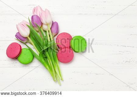 Tulip flowers and macaroon cookies over wooden background. Greeting card template with copy space