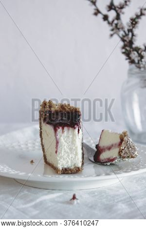 A Slice Of Homemade Cheesecake Drizzled With Currant Jam And Sprinkled With Crumbs In A Plate On A T