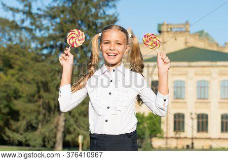 Smile Maker Snack. Happy Kid Hold Lollipops Outdoors. Little Girl Enjoy Candy Snack. Enjoying Snack