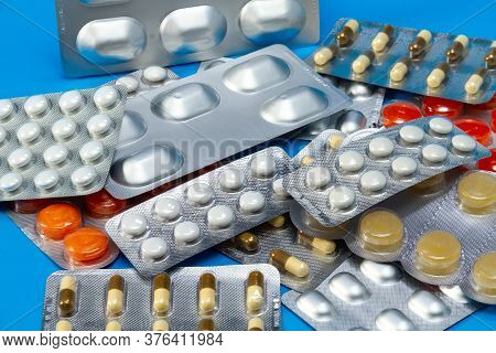 A Pile Of Pills In Blister Packs. The Blister Pack Is Full Of Multi-colored Tablets. A Pack Of Full-