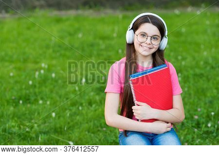 Affordable E-learning. Happy Kid Listen To E-learning Course. Small Girl Study Online Outdoors. E-le