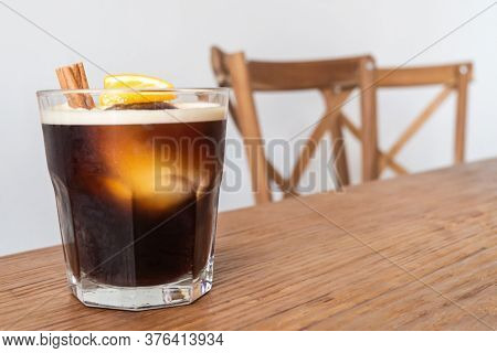 Nitro Cold Brew Coffee With Ice, Cinnamon And Lemon On Wooden Table And Chairs Set As A Special Drin