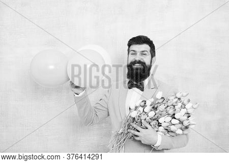 Present For Spouse. Guy With Air Balloons. Birthday Party. Bearded Man Hipster With Flower Bouquet.