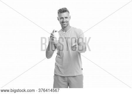 Health Product For You. Healthy Man Hold Pill Bottle. Fitness Coach Point Finger Isolated On White.