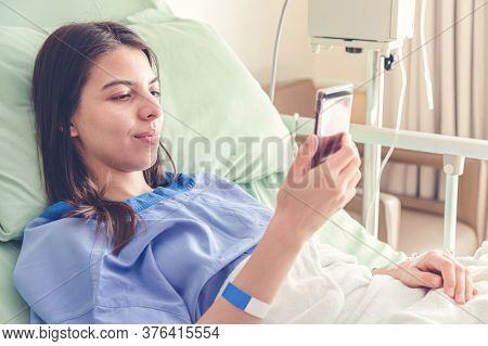 Beautiful Young Patient Women Lying In  Hospital Bed And Smiling With Smart Mobile Phone While Recov