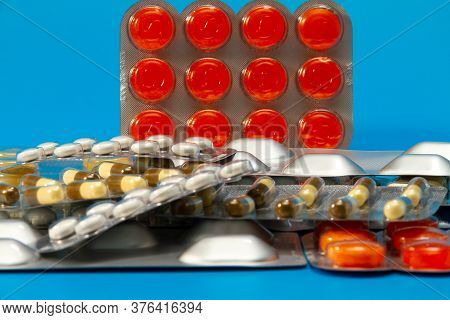 A Pile Of Pills In Blister Packs Close Up. Side View. The Blister Pack Is Full Of Multi-colored Tabl