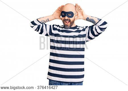Young handsome man wearing burglar mask smiling cheerful playing peek a boo with hands showing face. surprised and exited