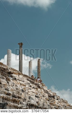 Couple sitting on the top of Ruins in Tyre. People Resting after Excursion along Necropolis in Lebanon. Visiting Famous Place. World Heritage. Active Summer Vacation.