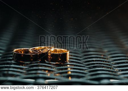Two Wedding Rings And One Engagement Ring On A Checkered Grid. Three Gold Rings Of A Couple In Love