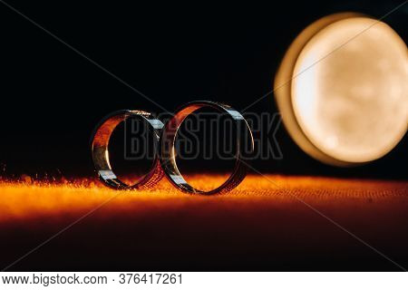 Two Wedding Rings On A Red Background. Gold Rings Of A Couple In Love.concept Of Love.wedding Ring