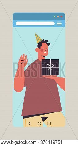 Man In Funny Festive Hat Celebrating Online Birthday Party Happy Guy In Smartphone Screen Holding Gi