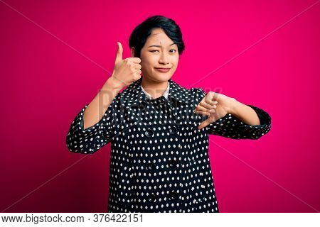 Young beautiful asian girl wearing casual jacket standing over isolated pink background Doing thumbs up and down, disagreement and agreement expression. Crazy conflict