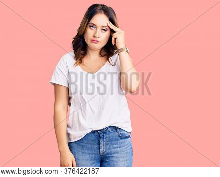 Young beautiful caucasian woman wearing casual white tshirt worried and stressed about a problem with hand on forehead, nervous and anxious for crisis