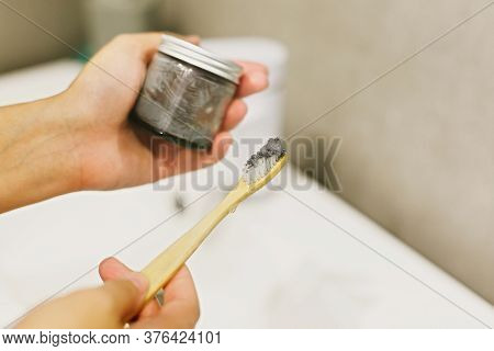 Zero Waste Bathroom Concept. Woman Using Bamboo Toothbrush And Charcoal Toothpaste From Glass Jar Fo
