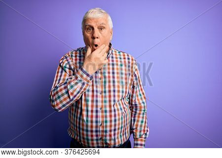 Senior handsome hoary man wearing casual colorful shirt over isolated purple background Looking fascinated with disbelief, surprise and amazed expression with hands on chin