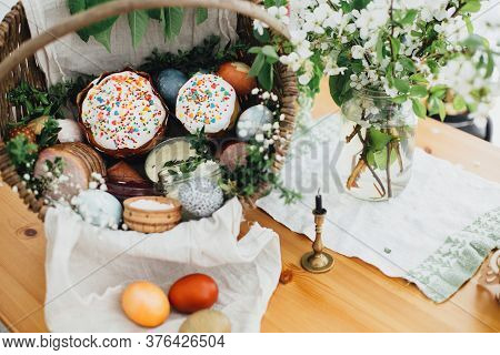 Easter Modern Eggs, Easter Bread, Ham, Beets, Butter, Sausages In Rustic Basket Decorated With Green
