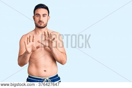 Young handsome man wearing swimwear moving away hands palms showing refusal and denial with afraid and disgusting expression. stop and forbidden.