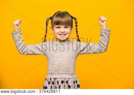 Positive Little Girl With Funny Pigtails Shows Her Power Biceps With Arms Raised Victory. Winner Sch