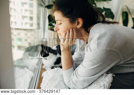Young Woman Looking At Window With Her Cat, Sitting At Home During Coronavirus Quarantine. Stay Home