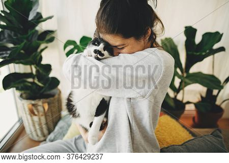 Happy Hipster Girl Hugging Cute Cat, Sitting Together At Home During Coronavirus Quarantine. Stay Ho
