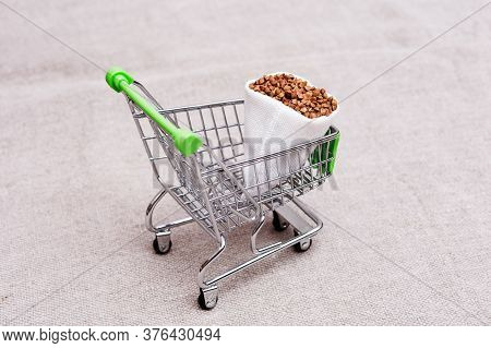 Shopping Cart With Full Sack Bag Of Buckwheat. Concept Of Large Consumer Demand For Buckwheat In Con