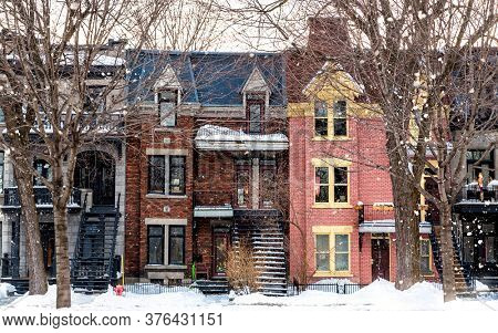 Winter street in Montreal, with traditional style architecture, snow covered balconies and heavy snowfall. Winter or Christmas themed seasonl image.