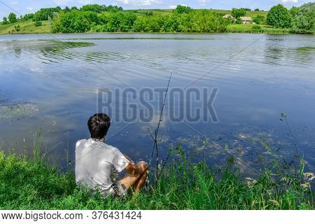 A Man Fishes Sitting In The Grass On The Coast Of The Pond On The Background Of Rural Houses On The